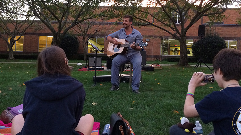 Male playing guitar outside.