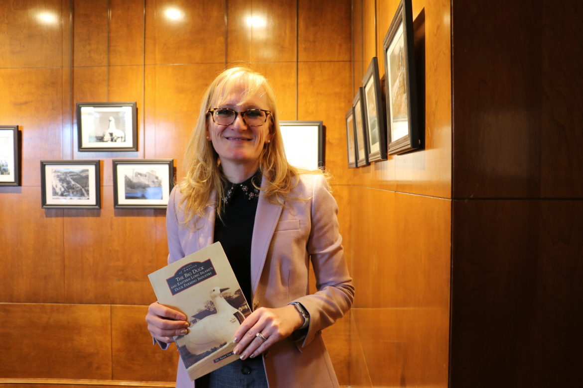 Dr. Heather Barry holding her copy of Dr. Van Scoy's book.